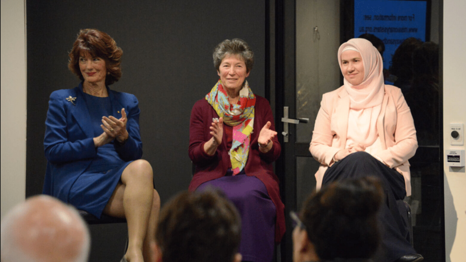Three women sitting on stage clapping