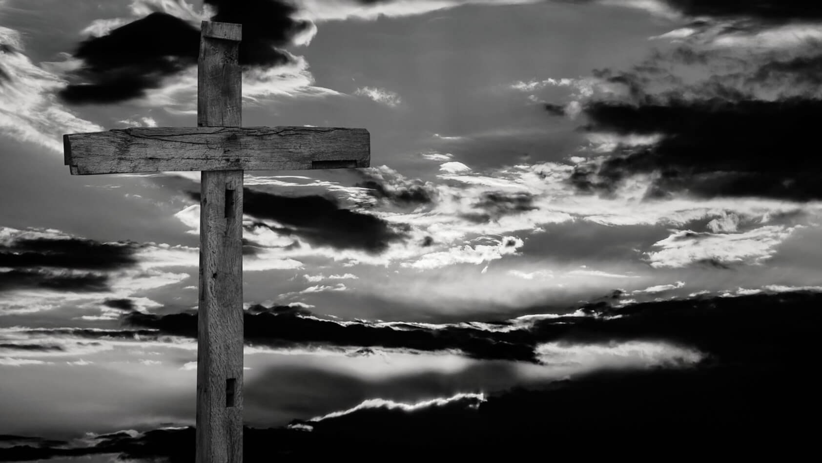 Cross with setting sun and clouds behind it