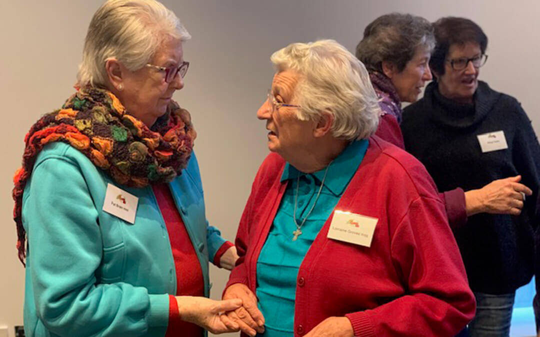 Two elderly women speaking to each other