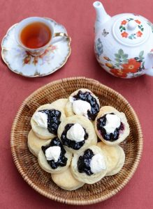 Bowl of scones with cream and jam and pot of tea and cup of tea