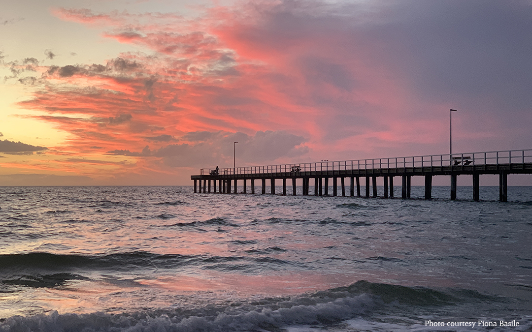 pink sunset over pier and water