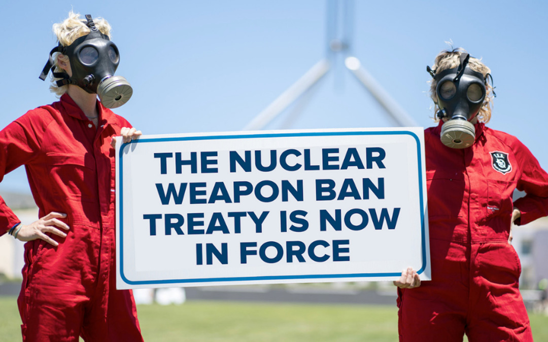 Two people in gas masks holding up Nuclear weapons ban sign