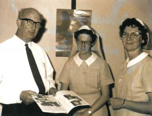 Man standing next to two nuns