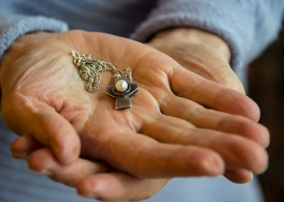 Hands holding necklace pendant with pearl
