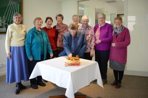 Group of women standing behind cake