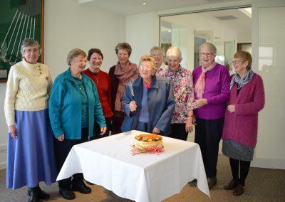 Women standing behind cake